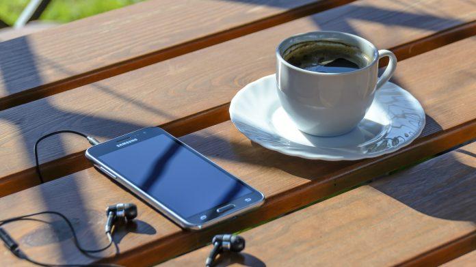 På ett soligt cafébord ligger en smartphone med inkopplade hörlurar bredvid fylld en kaffekopp.