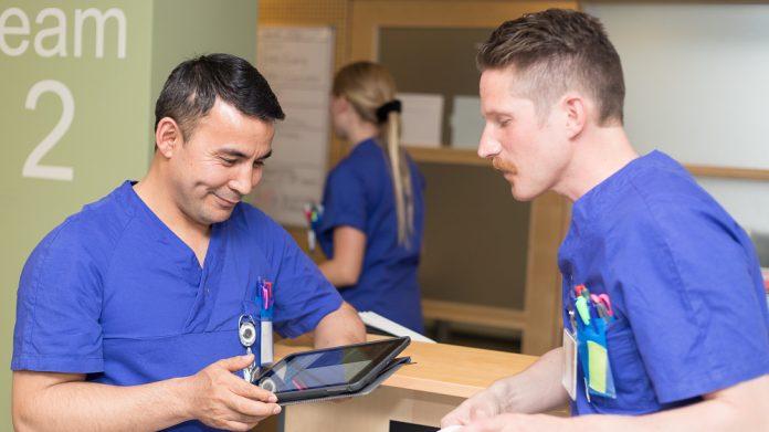 Sjuksköterskor med läsplatta och papper