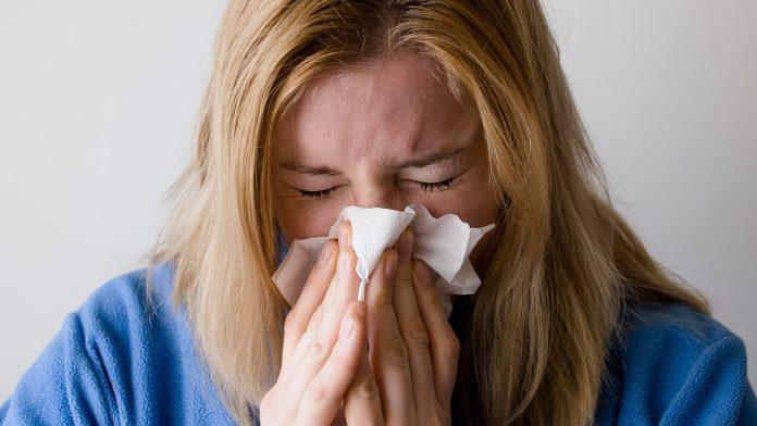 Kvinna som har influensa snyter sig