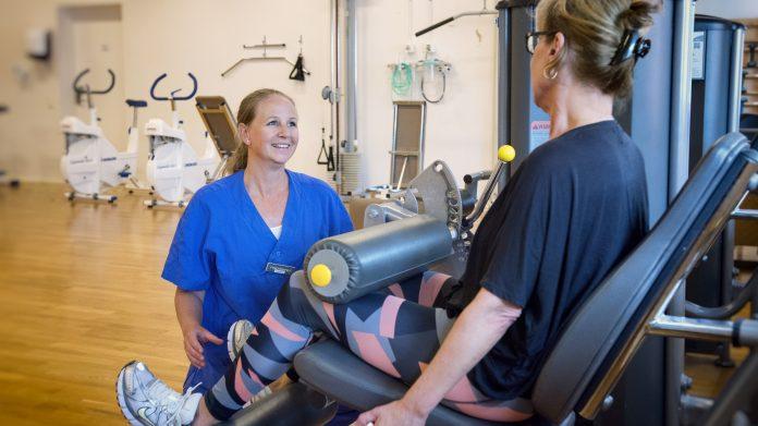 Fysioterapeuten Caroline pratar med en patient som sitter i en träningsmaskin