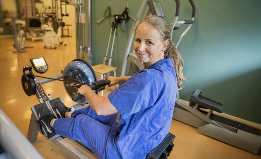 En kvinna sitter i en roddmaskin på ett gym