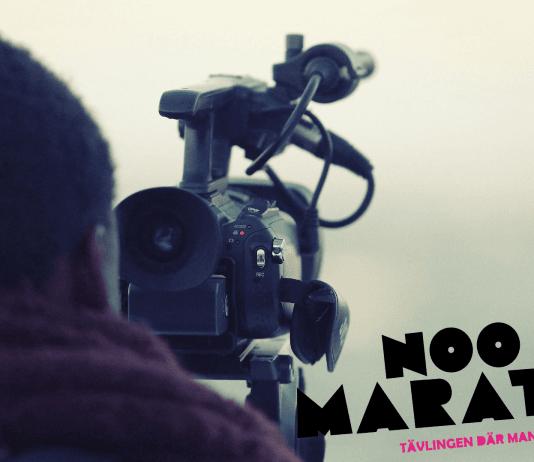 Bild på man som står med en filmnkamera.