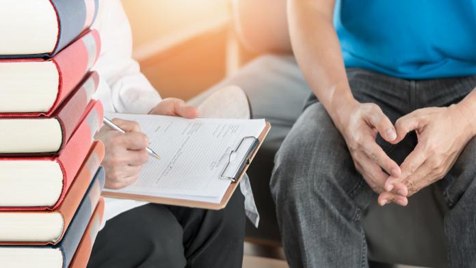 Bild p åböcker och en patient och läkare s händer som sitter i samtal