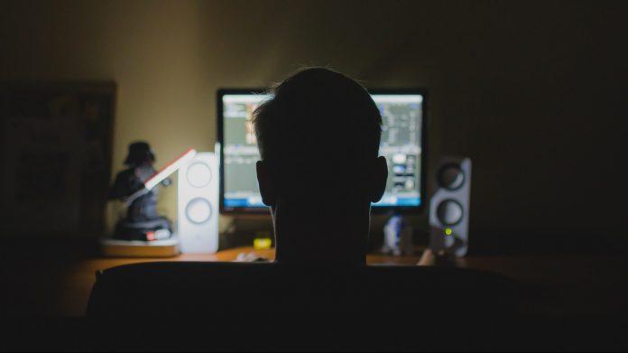 Bild på enman som sitter med ryggen mot kameran, framför en dator.