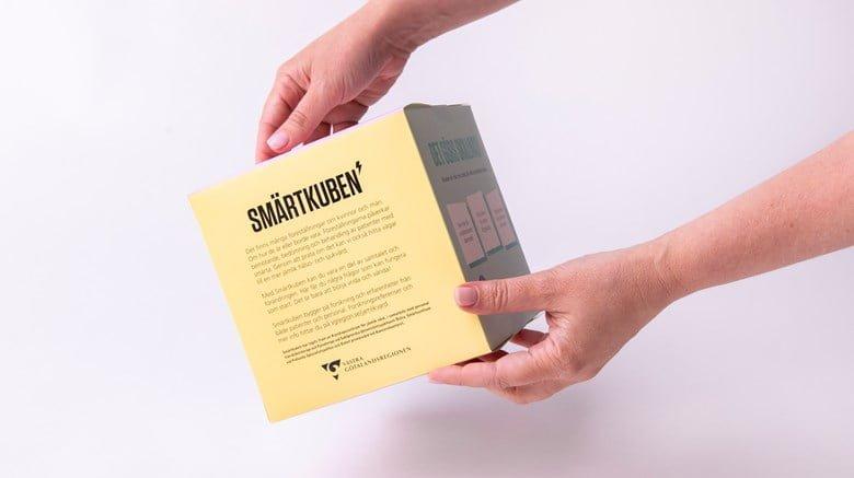 Bild på en fyrkantig papplåda med texten Smärtkub