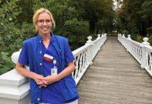 Bild på Susanne som står på en gångbro, lutar sig mot ett räcke, klädd i blå läkarklädsel.