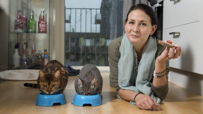 Hanna gör sällskap med katterna Mayo och Capri och tar en smörgås. Hon är noga med att äta sina mellanmål. Foto:Anna Rehnberg