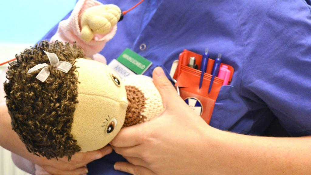 En docka hålls mot ett låtsasbröst i garn för att visa hur man håller en bebis som ammar.
