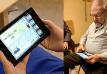 En äldre man kollar på en digital platta som hjälper honom att hålla kolla på sina hälsovärden.