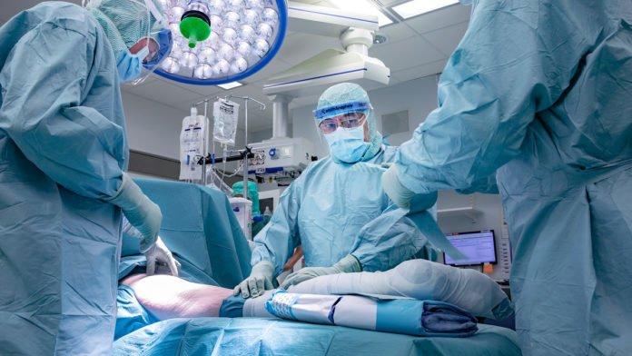 Bild på vårdpersonal, iklädda sterila skyddskläder och ansiktsmasker i en operationssal.