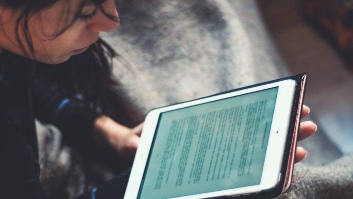En person sitter och läser en text på en surfplatta
