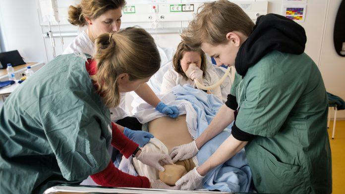 Barnmorskan Linda Ivansson instruerar Agnes Frimannsson och Eben Weilenmann under en simulerad förlossning på Simulatorcentrum. Foto: Anna Rehnberg