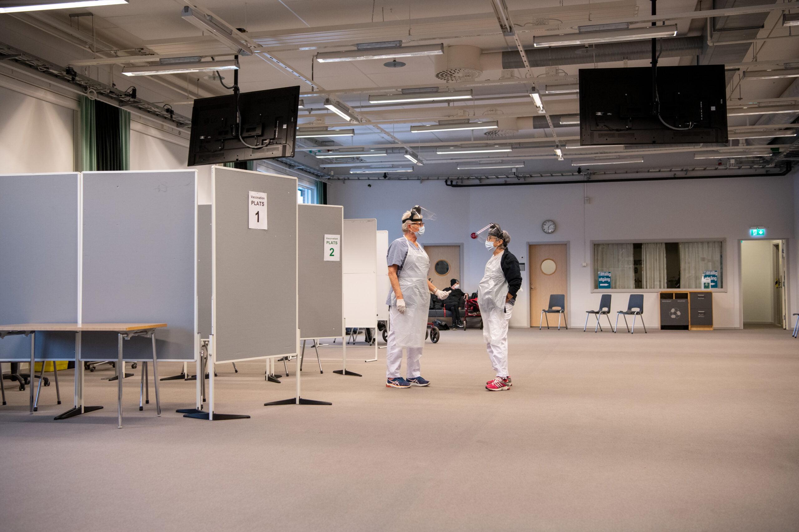 I lokalerna som Högskolan Väst lånar ut finns gott om plats så att vaccineringen kan flyta på både smidigt och smittsäkert.<br /> De vaccinerande sjuksköterskorna Birgitta Bondeson och Viola Svensson väntar på fler patienter. I bakgrunden syns efterväntrummet innanför den tillfälliga utgången. Foto: Kent Eng.