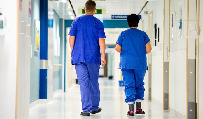 Vårdpersonal som går i en sjukhuskorridor.