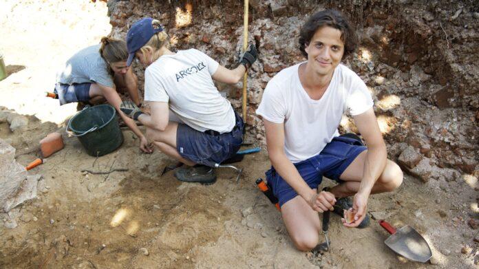 Anton Lazarides är fältarbetsledare under utgrävningarna i Edsleskog, där resterna av Sveriges äldsta tegelkyrka grävts fram under sammanlagt tre veckor. I bakgrunden syns Nora Hansson (tv) och Anna Beckman. Foto: Kent Eng