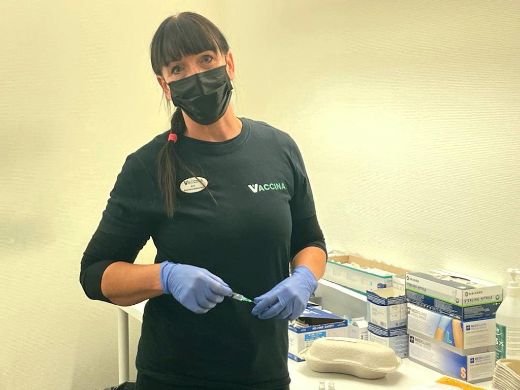 Ana Cagnais, distrikts- och IVA sköterska och platsansvarig för verksamheten hos Vaccina i Skövde står utrustad för vaccination med en vaccinationsspruta i handen iförd munskydd och handskar.