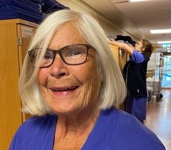 Britt Svensson, distriktssköterska på Närhälsan Tjörn står arbetsklädd i en korridor på sin arbetsplats