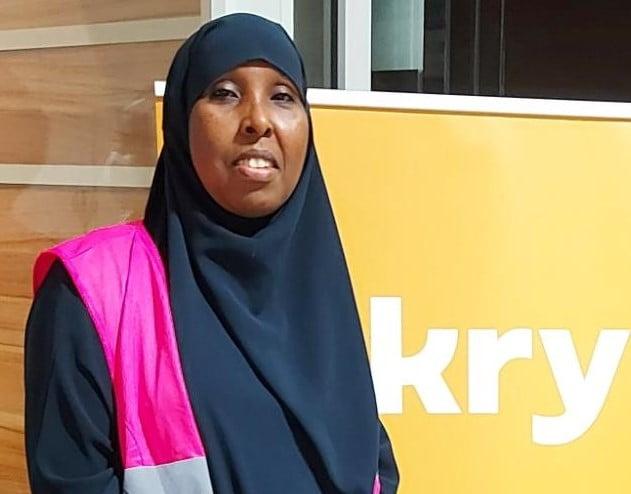 Saido Mohamed jobbar som kulturtolk i Göteborg. Hon står i rosa reflexväst vid en skylt som det står Kry på.