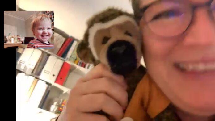 En kvinna som leker titt ut med sitt barnbarn via video.