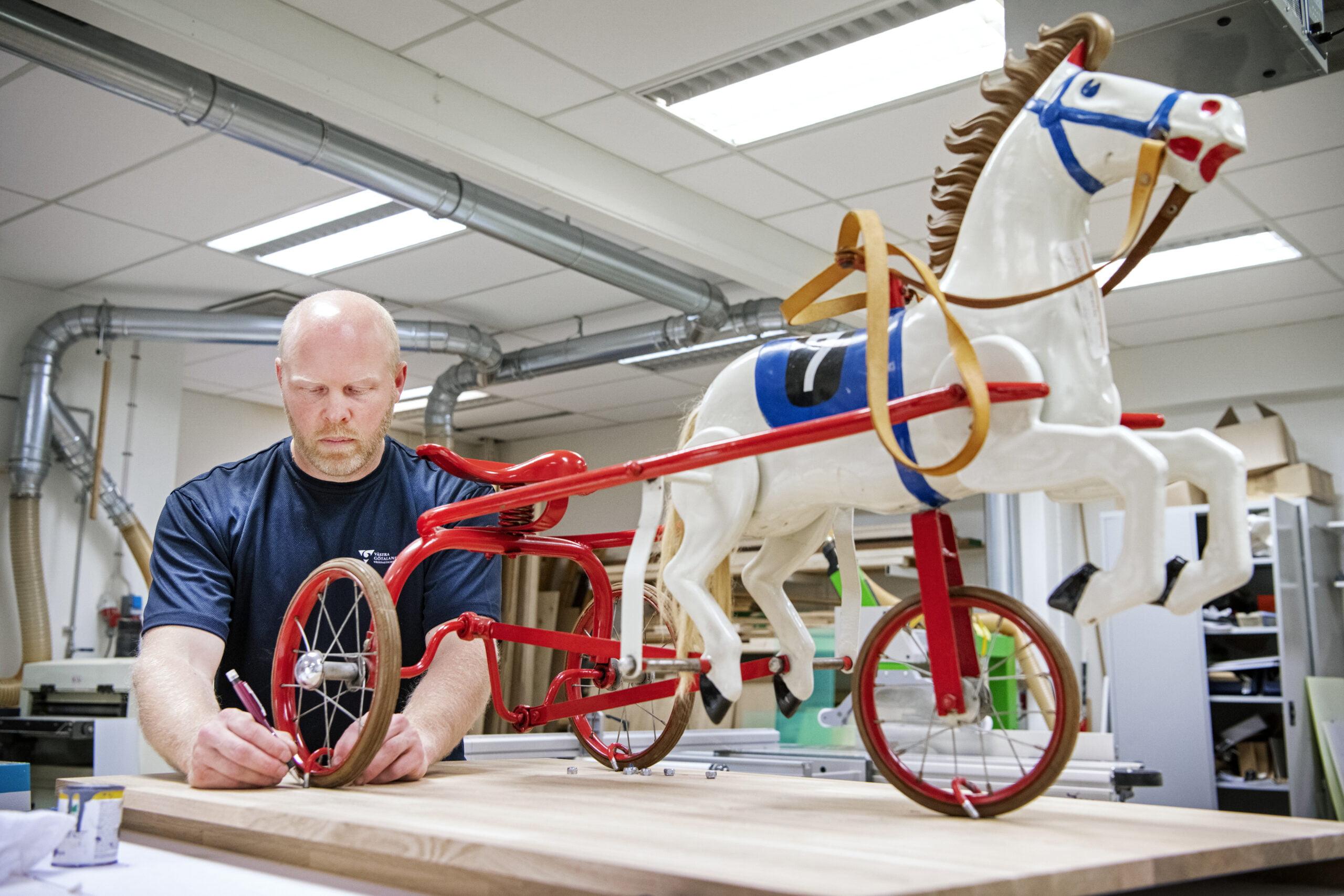 Hans Persson monterar leksakshästen på en låg sockel av ek. Hästen ska till en barn- och ungdomspsykiatrisk mottagning i Borås. Den ska tåla att klättras på, men måste monteras fast ordentligt så det inte går att köra iväg med den. Foto: Kent Eng.