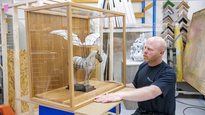Vit flygare, en skulptur av Marta Runemark, har fått ett vägghängt skåp i ek och glas. Den kommer snart att hänga på en folktandvårdsklinik i Boråsområdet. Foto: Kent Eng