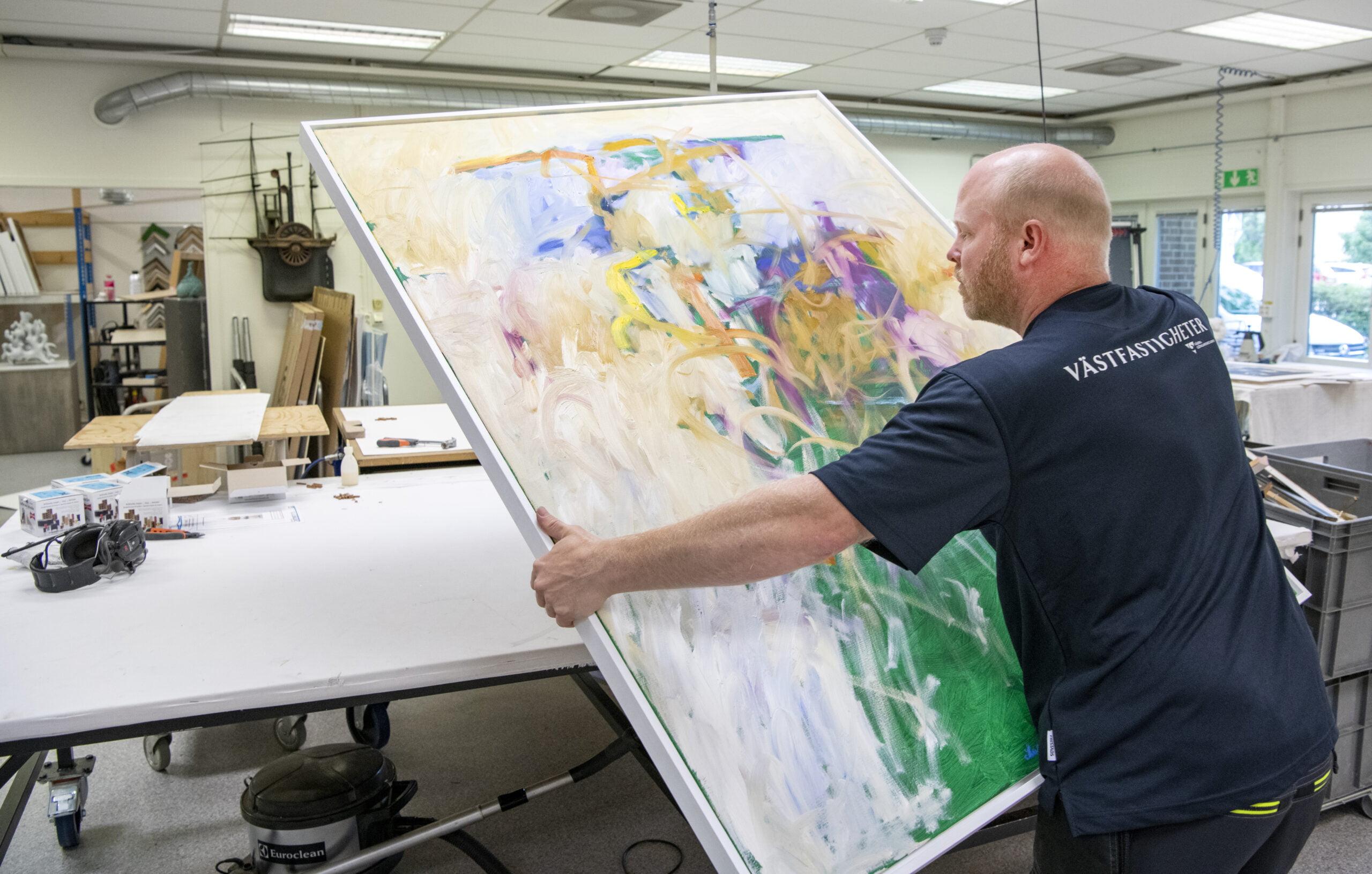 En stor oljemålning av Vänersborgskonstnären Bengt Johansson har kommit in för att få en ny ram. Foto: Kent Eng