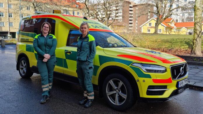 Sjuksköterskorna Ida Larsson och Karin Hermansson, ambulansen Trestad Öst, framför en ambulans.