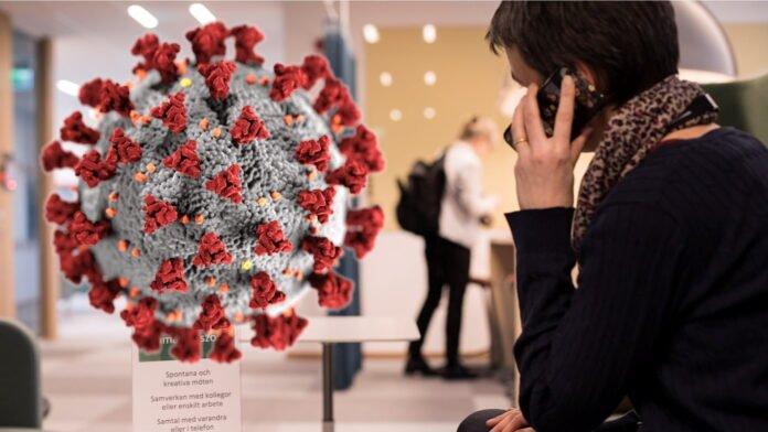En kvinna talar i telefon. Ovanför henne syns ett fiktivt covid-19-virus.