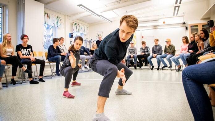 Personer som dansar i ett klassrum och några ser på. Bilden är från en skolföreställning med Regionteater Väst.
